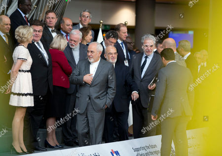 Iranian Foreign Minister Mohammad Javad Zarif, center left, and Iraq's Foreign Minister Ibrahim al-Jaafari, center right, arrive for a group photo at a conference 'Supporting the future of Syria and the region' at the Europa building in Brussels on . EU foreign policy chief Federica Mogherini is calling on Russia, Iran and Turkey to force a halt to fighting in Syria, as international donors gather in Brussels to drum up aid for the conflict-ravaged country
