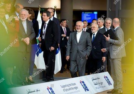 Iranian Foreign Minister Mohammad Javad Zarif, center left, and Iraq's Foreign Minister Ibrahim al-Jaafari, center right, speak with a member of protocol as they arrive for a group photo at a conference 'Supporting the future of Syria and the region' at the Europa building in Brussels on . EU foreign policy chief Federica Mogherini is calling on Russia, Iran and Turkey to force a halt to fighting in Syria, as international donors gather in Brussels to drum up aid for the conflict-ravaged country