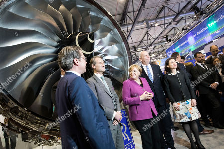 (R-L) French Junior Minister for Economy Delphine Geny-Stephann, Minister President of Brandenburg Dietmar Woidke, German Chancellor Angela Merkel, Rolls Royce Marketing Director Ben Story, German Minister of Transportation Andreas Scheuer  stand in front of a Rolls Royce engine at the MTU booth at the ILA Berlin Air Show 2018 in Selchow, Germany, 25 April 2018. The aerospace and defense industry exhibition takes place at the inactive Berlin-Brandenburg airport from 25 April 25 to the 29 April, 2018.