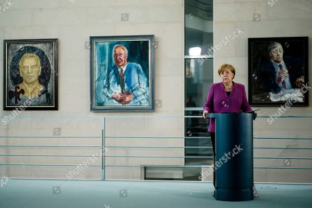 German Chancellor Angela Merkel delivers her speech as she attends an event at the eve of the international 'Girl's Day' at the chancellery in Berlin, . in the background paintings of her predecessors from left Gerhard Schroeder, Helmut Kohl and Helmut Schmidt