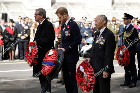 Britain's Prince Harry waits to lay a wreath flanked by Australian High Commissioner to Britain Alexander Downer, left, and New Zealand High Commissioner to Britain Jerry Mateparae during an ANZAC Day service at the Cenotaph in London,. ANZAC Day commemorates the moment when Australian and New Zealand Army Corps troops waded ashore at the Gallipoli peninsula in Turkey 103 years ago in their first major battle of World War I
