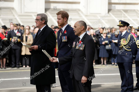 New Zealand High Commissioner to Britain Jerry Mateparae, right, shares his order of service with Britain's Prince Harry as they sing flanked by Australian High Commissioner to Britain Alexander Downer, left, and during an ANZAC Day service at the Cenotaph in London,. ANZAC Day commemorates the moment when Australian and New Zealand Army Corps troops waded ashore at the Gallipoli peninsula in Turkey 103 years ago in their first major battle of World War I