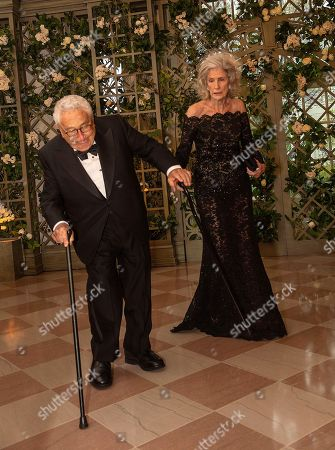 Former Secretary of State Henry Kissinger stumbles upon arriving with Mrs. Nancy Kissinger at they arrive for the State Dinner