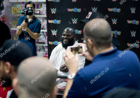 Professional wrestler Mark Henry poses for fans as he signs posters during a ceremony in Jiddah, Saudi Arabia, two days before the Greatest Royal Rumble will kick off