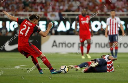 Toronto FC's Jonathan Osorio, left, fights for the ball with Chivas' Carlos Salcido during the CONCACAF Champions League final soccer match in Guadalajara, Mexico, Wednesday, April, 25, 2018