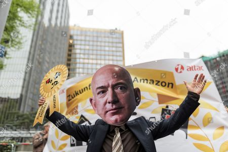 A demonstrator of a Jeff Bezos holds a Symbolic Award in the air during the demonstration against the awarding of the Axel Springer Award 2018 to Amazon founder Jeff Bezos for his 'visionary entrepreneurship'
