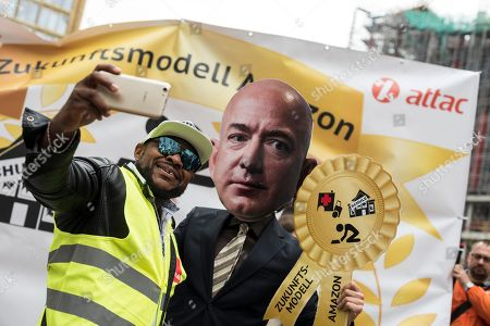 A protester makes a selfie with a demonstrator wearing a Jeff Bezo's mask during the demonstration against the awarding of the Axel Springer Award 2018 to Amazon founder Jeff Bezos for his 'visionary entrepreneurship'