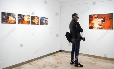 Stock Picture of A photographer visits the exhibition 'World Press Photo' 2018 in Seville, Spain, 26 April 2018. The World Press Photo of the Year contest winner is Venezuelan photojournalist Ronaldo Schemidt with his picture (R) of a demonstrator catching fire during clashes with riot police at an anti-government protest in Caracas, Venezuela on 03 May 2017.