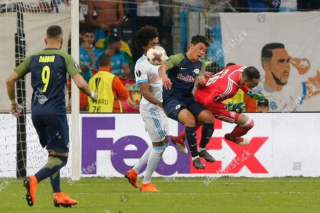 Marseille's Luiz Gustavo, left, Salzburg's Hee-Chan Hwang, center, and Marseille goalkeeper Yohann Pele challenge for the ball during the Europa League semifinal first leg soccer match between Olympique Marseille and RB Salzburg at the Velodrome stadium in Marseille, France