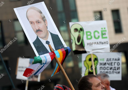 A portrait of Belarussian President Aleksandr Lukashenko and posters are seen during a rally to mark the 32nd anniversary of the Chernobyl nuclear disaster in Minsk, Belarus, 26 April 2018. The 32nd anniversary of the Ukrainian, Chernobyl nuclear disaster is marked on 26 April 2018. The poster reads 'Do nothing. Sit down and keep quiet', 'Everything is normal'.