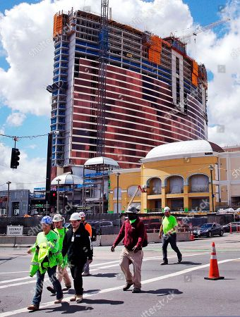 Construction workers leave at the end of their shift at the Wynn Resorts casino site in Everett, Mass., . Massachusetts gambling regulators consider Wynn Resorts' request to remove the name of company founder Steve Wynn, who faces numerous allegations of sexual misconduct, from its state casino license