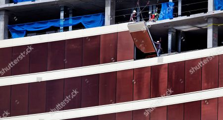 Construction workers install glass panels on the facade at the Wynn Resorts casino site in Everett, Mass., . Massachusetts gambling regulators consider Wynn Resorts' request to remove the name of company founder Steve Wynn, who faces numerous allegations of sexual misconduct, from its state casino license
