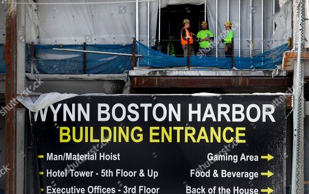 Workers talk on a floor under construction at the Wynn Resorts casino site in Everett, Mass., . Massachusetts gambling regulators consider Wynn Resorts' request to remove the name of company founder Steve Wynn, who faces numerous allegations of sexual misconduct, from its state casino license