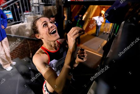 Jenny Simpson celebrates with fans as she leaves the track after winning the women's special 2-mile run at the Drake Relays athletics meet, in Des Moines, Iowa