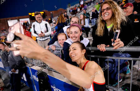 Jenny Simpson takes a selfie with fans as she leaves the track after winning the women's special 2-mile run at the Drake Relays athletics meet, in Des Moines, Iowa