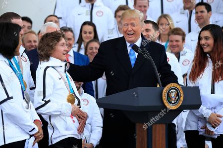 Donald Trump, Redmond Gerard. Olympic gold medalist snowboarder Redmond Gerard, left, listens to President Donald Trump describing his snowboarding stunts during a ceremony welcoming the Team USA Olympic athletes on North Portico at the White House in Washington
