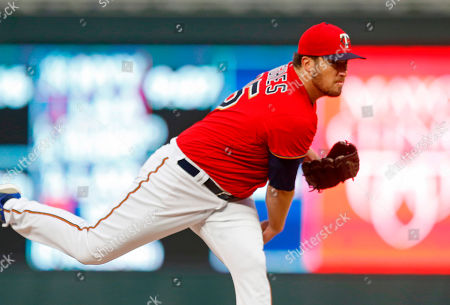 Minnesota Twins pitcher Phil Hughes throws against the Cincinnati Reds in the first inning of a baseball game, in Minneapolis