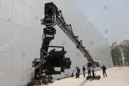 Film crew staff use a camera crane rig to record footage at Wanda Film Industrial Park of Wanda Oriental Movie Metropolis in Qingdao, Shandong province, China, 28 April 2018. Wanda Qingdao Oriental Movie Metropolis opens on 28 April 2018 which is a major Chinese studio, combining film and television production and several other facilities which was funded by Wang Jianlin, CEO of the Dalian Wanda Group. Starting construction on 22 September 2013 with the total investment of 50 billion RMB yuan (around 6.5 billion Euros), it has the world's largest studio pavilion of 10,000 square meters, featuring some of the world's largest and most technologically-advanced facilities.