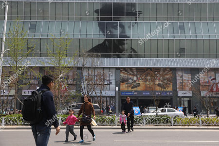 People walk near the Wanda Mall, a part of Wanda Oriental Movie Metropolis in Qingdao, Shandong province, China, 28 April 2018. Wanda Qingdao Oriental Movie Metropolis opens on 28 April, a major Chinese studio, combining film and television production and several other facilities, funded by Wang Jianlin, CEO of the Dalian Wanda Group. The construction of the facility started on 22 September 2013, with the total investment of 50 billion RMB yuan (around 6.5 billion Euros), it has the world's largest studio pavilion of 10,000 square meters, featuring some of the world's largest and most technologically-advanced facilities.