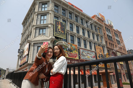 People take a selfie near buildings that are a part of the Wanda Oriental Movie Metropolis in Qingdao, Shandong province, China, 28 April 2018. Wanda Qingdao Oriental Movie Metropolis opens on 28 April, a major Chinese studio, combining film and television production and several other facilities, funded by Wang Jianlin, CEO of the Dalian Wanda Group. The construction of the facility started on 22 September 2013, with the total investment of 50 billion RMB yuan (around 6.5 billion Euros), it has the world's largest studio pavilion of 10,000 square meters, featuring some of the world's largest and most technologically-advanced facilities.