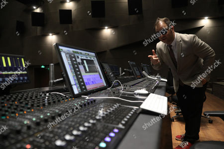 A producer performs audio adjustments at a film post-production studio at Wanda Film Industrial Park of Wanda Oriental Movie Metropolis in Qingdao, Shandong province, China, 28 April 2018. Wanda Qingdao Oriental Movie Metropolis opens on 28 April, a major Chinese studio, combining film and television production and several other facilities, funded by Wang Jianlin, CEO of the Dalian Wanda Group. The construction of the facility started on 22 September 2013, with the total investment of 50 billion RMB yuan (around 6.5 billion Euros), it has the world's largest studio pavilion of 10,000 square meters, featuring some of the world's largest and most technologically-advanced facilities.