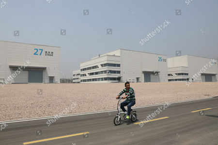 A man rides a bicycle past the film studio pavilions at Wanda Film Industrial Park of Wanda Oriental Movie Metropolis in Qingdao, Shandong province, China, 28 April 2018. Wanda Qingdao Oriental Movie Metropolis opens on 28 April, a major Chinese studio, combining film and television production and several other facilities, funded by Wang Jianlin, CEO of the Dalian Wanda Group. The construction of the facility started on 22 September 2013, with the total investment of 50 billion RMB yuan (around 6.5 billion Euros), it has the world's largest studio pavilion of 10,000 square meters, featuring some of the world's largest and most technologically-advanced facilities.