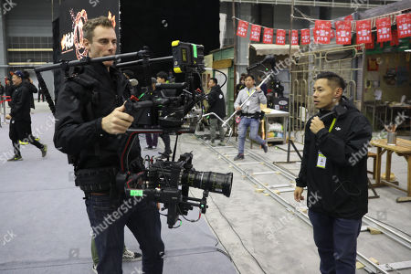 A cameraman operates a camera in a 10,000-square-meter film studio pavilion of Wanda Oriental Movie Metropolis in Qingdao, Shandong province, China, 28 April 2018. Wanda Qingdao Oriental Movie Metropolis opens on 28 April, a major Chinese studio, combining film and television production and several other facilities, funded by Wang Jianlin, CEO of the Dalian Wanda Group. The construction of the facility started on 22 September 2013, with the total investment of 50 billion RMB yuan (around 6.5 billion Euros), it has the world's largest studio pavilion of 10,000 square meters, featuring some of the world's largest and most technologically-advanced facilities.