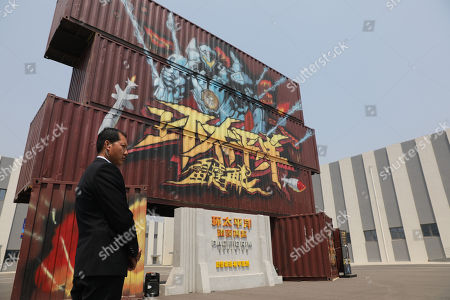 A security guard stands in front of the film studio pavilions at Wanda Film Industrial Park of Wanda Oriental Movie Metropolis in Qingdao, Shandong province, China, 28 April 2018. Wanda Qingdao Oriental Movie Metropolis opens on 28 April, a major Chinese studio, combining film and television production and several other facilities, funded by Wang Jianlin, CEO of the Dalian Wanda Group. The construction of the facility started on 22 September 2013, with the total investment of 50 billion RMB yuan (around 6.5 billion Euros), it has the world's largest studio pavilion of 10,000 square meters, featuring some of the world's largest and most technologically-advanced facilities.