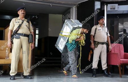 Indian security personnel stand as a labourer (C) carries boxes containing official records of Jammu and Kashmir state's Civil Secretariat, for loading into the trucks in Jammu, the winter capital of Kashmir, India, 28 April 2018. Jammu and Kashmir is the only state in India where 'Darbar' (government offices of all departments) are shifted bi-annually between the two state capitals. The offices remain functional for six winter months in Jammu which is the winter capital of the state and again are shifted back to Srinagar which is state's summer capital during summers. The trend of shifting state secretariat from one state capital to another has been going on in the state since 1872, the era of Maharaja Gulab Singh.