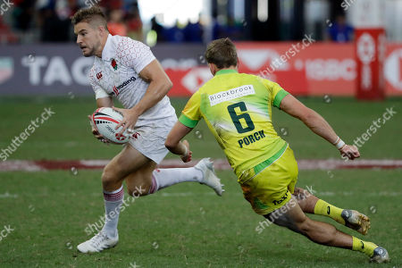 England's Tom Mitchell, breaks away to score a try as Australia's John Porch, right, runs after him during the HSBC World Rugby Sevens Series 2018 semi-final match, in Singapore