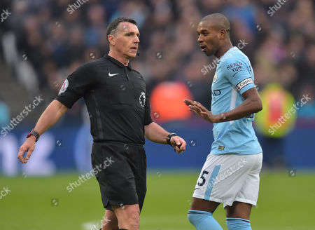 Stock Photo of Fernandinho of Manchester City talks with Referee Neil Swarbrick about his decision not to award a penalty