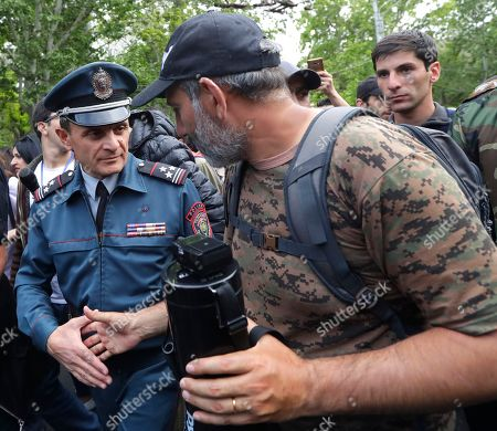 Armenian protest leader Nikol Pashinian, right, shakes hands with police officer in Yerevan, Armenia, . Nikol Pashinian said Sunday that he hopes President Armen Sarkisian will support Pashinian's bid to become prime minister. The parliament is to choose a new premier on Tuesday, following the resignation last week of Serzh Sargsyan
