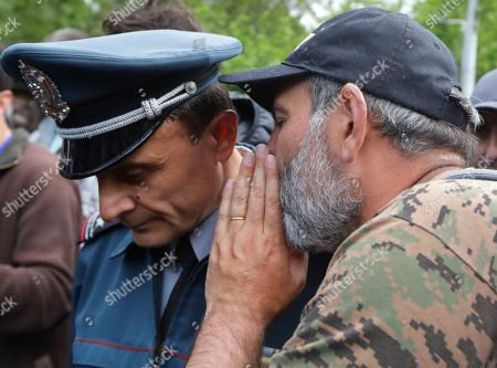 Armenian protest leader Nikol Pashinian, right, speaks with a police officer in Yerevan, Armenia, . Nikol Pashinian said Sunday that he hopes President Armen Sarkisian will support Pashinian's bid to become prime minister. The parliament is to choose a new premier on Tuesday, following the resignation last week of Serzh Sargsyan