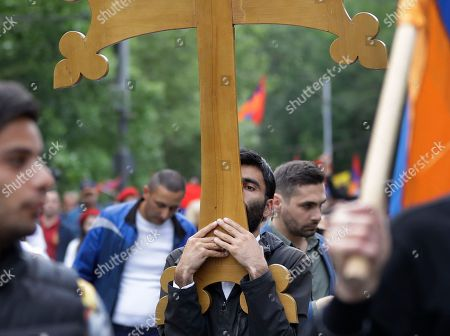A man carries a wooden cross as protesters march to Republic Square in Yerevan, Armenia, . The leader of the wave of protests that has pushed Armenia into a political crisis says he has met with the country's president. Nikol Pashinian said Sunday that he hopes President Armen Sarkisian will support Pashinian's bid to become prime minister. The parliament is to choose a new premier on Tuesday, following the resignation last week of Serzh Sargsyan