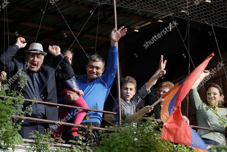 People wave at protestors from their balcony in Yerevan, Armenia, . The leader of the wave of protests that has pushed Armenia into a political crisis says he has met with the country's president. Nikol Pashinian said Sunday that he hopes President Armen Sarkisian will support Pashinian's bid to become prime minister. The parliament is to choose a new premier on Tuesday, following the resignation last week of Serzh Sargsyan