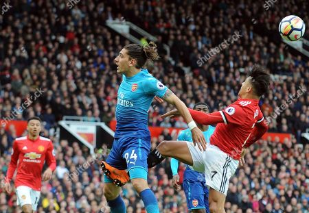 Manchester United's Alexis Sanchez, right, challenges for the ball with Arsenal's Hector Bellerin during the English Premier League soccer match between Manchester United and Arsenal at the Old Trafford stadium in Manchester, England