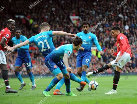 Manchester United's Jesse Lingard, right, duels for the ball with Calum Chambers, left, and Arsenal's Hector Bellerin, front center, during the English Premier League soccer match between Manchester United and Arsenal at the Old Trafford stadium in Manchester, England