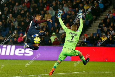 Guingamp goalkeeper Karl-Johan Johnsson, right, makes a save in front of PSG's Kylian Mbappe during the French League One soccer match between Paris Saint Germain and Guingamp at the Parc des Princes stadium in Paris