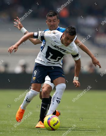 Pumas' Pablo Barrera, front, fights for the ball with Queretaro's Edgar Benitez during a Mexican soccer league match in Mexico City, . Pumas and Queretaro tied 1-1