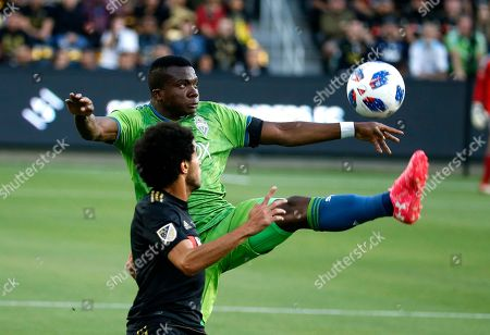 Seattle Sounders defender Nouhou (5) of Cameroon, kicks the ball against Los Angeles FC defender Omar Gaber (4) of Egypt, in the first half of an MLS soccer game at Banc of California Stadium in Los Angeles