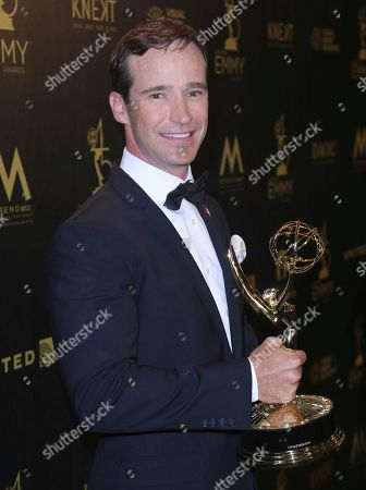 """Mike Richards poses in the press room with the award for outstanding game show for """"The Price is Right"""""""