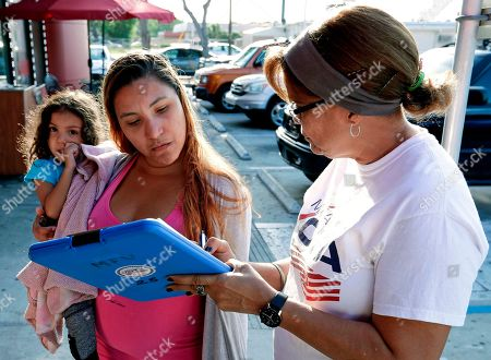 Stock Photo of Michelle Ortiz, who was born in New York to Puerto Rican parents and recently moved to Florida, holds her daughter as she registers to vote with the help of volunteer Carmina Redonet, right, in Orlando, Florida. Political operatives, pollsters and politicians in at least four states are working hard right now to find Puerto Ricans who are eligible to vote and whose party affiliation may be up for grabs