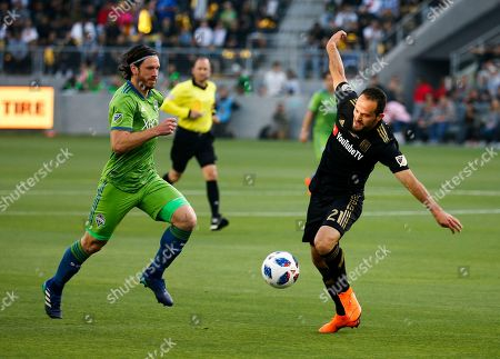 Seattle Sounders midfielder Gustav Svensson (4) of Sweden, vies with Los Angeles FC forward Marco Urena (21) of Costa Rica, in the first half of an MLS soccer game at Banc of California Stadium in Los Angeles