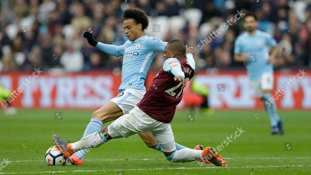 Manchester City's Leroy Sane, left is tackled by West Ham United's Patrice Evra during the English Premier League soccer match between West Ham United and Manchester City at the London stadium in London, Sunday, April, 29, 2018