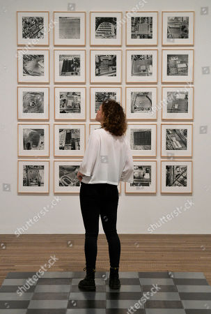 Stock Image of A woman poses with the work 'Parking Lots'  by US artist Edward Ruscha during a press preview of the exhibition 'Shape of Light: 100 Years of Photography and Abstract Ar' at the Tate Modern in London, Britain, 30 April 2018. The exhibition features over 350 works by 100 artists and explores photography in relation to the development of abstraction. The show run from 02 May to 14 October 2018.