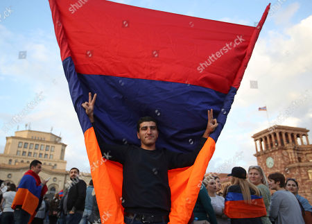A supporter of the opposition lawmaker Nikol Pashinian gestures as he holds a large Armenian flag during a rally in Yerevan on . Armenia's parliament plans to choose a replacement on Tuesday for Serzh Sargsyan, who resigned last week amid the street demonstrations over his selection as prime minister. Pashinian, who led the protests, hopes to be the next premier