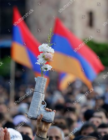 A supporter of Armenian protest leader Nikol Pashinian holds up a fake gun with flowers during a rally in Yerevan on . Armenia's parliament plans to choose a replacement on Tuesday for Serzh Sargsyan, who resigned last week amid the street demonstrations over his selection as prime minister. Pashinian, who led the protests, hopes to be the next premier