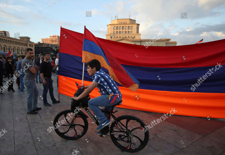 Young boy rides his bike with supporters of the opposition lawmaker Nikol Pashinian who hold a large Armenian flag during a rally in Yerevan on . Armenia's parliament plans to choose a replacement on Tuesday for Serzh Sargsyan, who resigned last week amid the street demonstrations over his selection as prime minister. Pashinian, who led the protests, hopes to be the next premier
