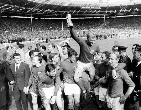 England captain Bobby Moore holds the World Cup aloft as he is chaired by his jubilant teammates: (l-r) Nobby Stiles, Martin Peters (front), Jack Charlton (back), Alan Ball, Gordon Banks, Geoff Hurst, Roger Hunt (hidden behind Hurst), Bobby Moore, Ray Wilson, George Cohen, Bobby Charlton. Other members of the England squad in the picture are Jimmy Greaves (background, far l), Ron Flowers (background, second l), Terry Paine (l of Stiles), Gerry Byrne (behind Bobby Charlton's head)