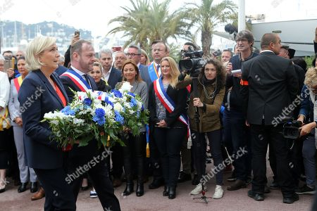 President of the French far-right Front National (FN) party Marine Le Pen (L) and vice president of the FN party and mayor of Henin-Beaumont Steeve Briois (R), carry a spray of flowers in order to place it under the statue of Joan of Arc - Jeanne D'Arc during a May Day rally in honour of the French historical figure, in Cannes